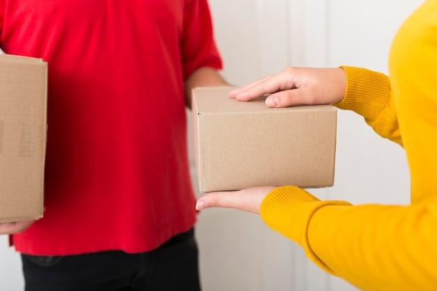 Frau, die ein paket vom lieferboten nimmt