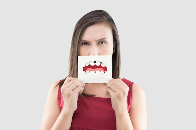 Frau, die ein papier mit defekter zahnkarikatur hält