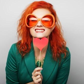 Frau, die ein partyherz und eine brille hält.