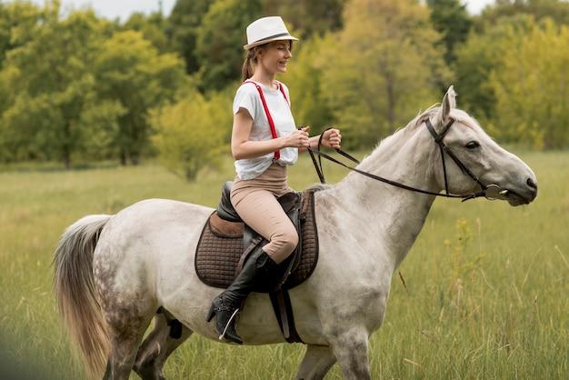 Frau, die ein pferd in der landschaft befreit