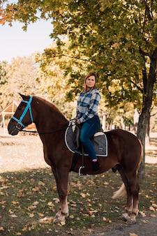 Frau, die ein pferd reitet, das im herbstpark spazieren geht