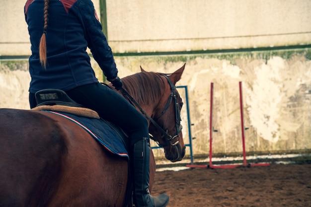 Frau, die ein pferd reitet, das von hinten geschossen wird