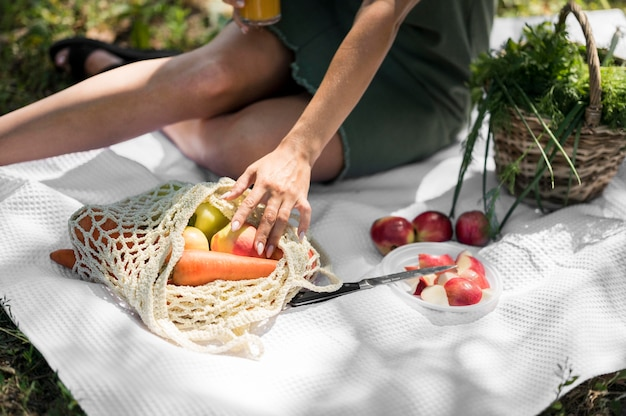 Frau, die ein picknick mit gesunden snacks hat