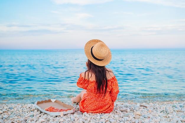 Frau, die ein picknick mit pizza am strand hat
