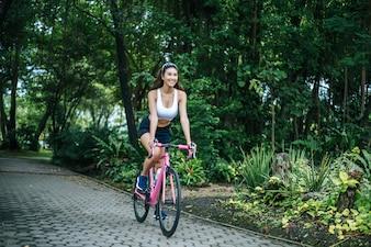 Frau, die ein Rennrad im Park reitet. Portrait der jungen schönen Frau auf rosafarbenem Fahrrad.