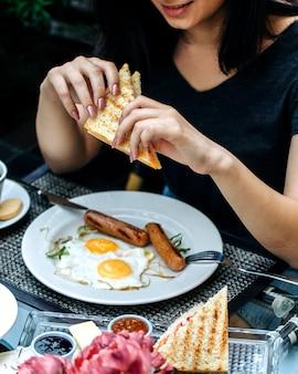 Frau, die ein sandwich am tisch isst