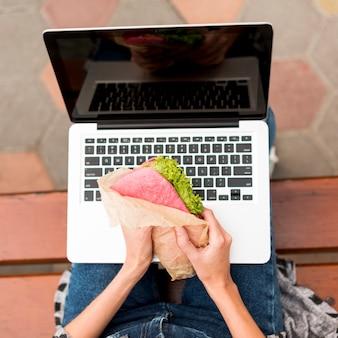 Frau, die ein sandwich vor laptop hält