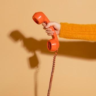 Frau, die ein schnurgebundenes retro-telefon beantwortet