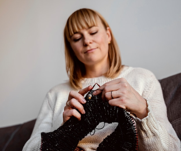 Frau, die ein schwarzes fadenzubehör strickt