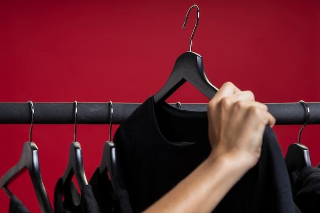 Frau, die ein schwarzes hemd betrachtet