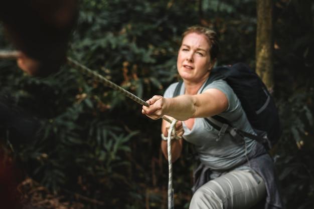 Frau, die ein seil klettert