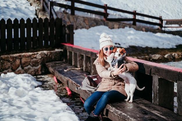Frau, die ein selbstporträt mit ihrem niedlichen hund draußen nimmt. technologie- und haustierkonzept
