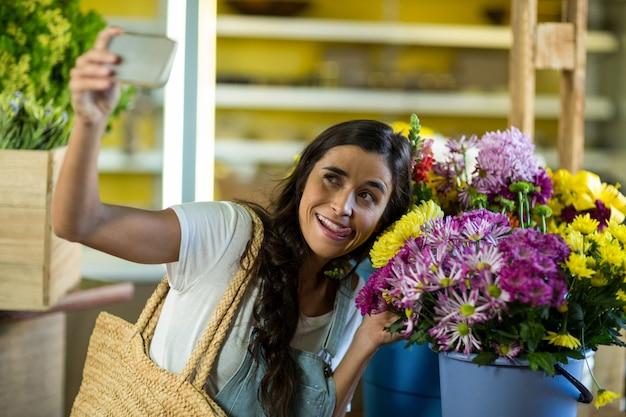 Frau, die ein selfie am blumengeschäft nimmt