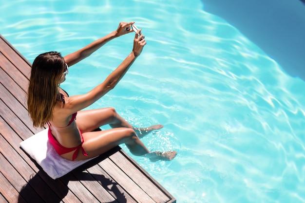 Frau, die ein selfie am poolrand nimmt