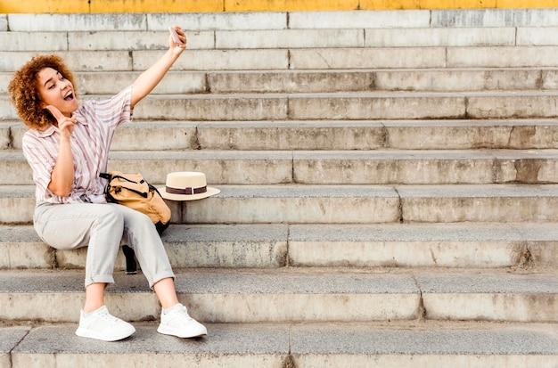 Frau, die ein selfie auf der treppe mit kopienraum nimmt