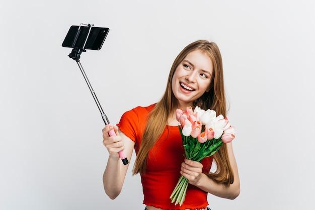 Frau, die ein selfie beim halten eines blumenstraußes der tulpen nimmt