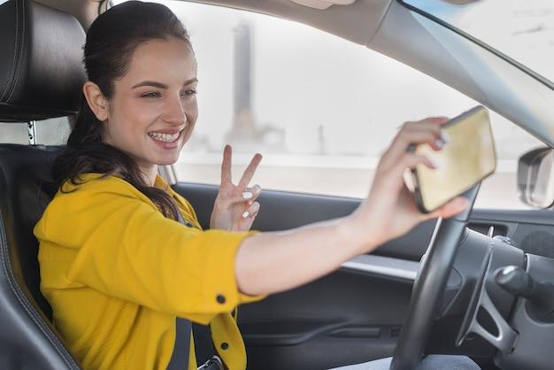 Frau, die ein selfie im auto nimmt