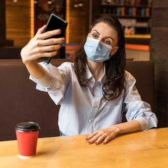 Frau, die ein selfie in einem restaurant nimmt, während sie eine medizinische maske trägt