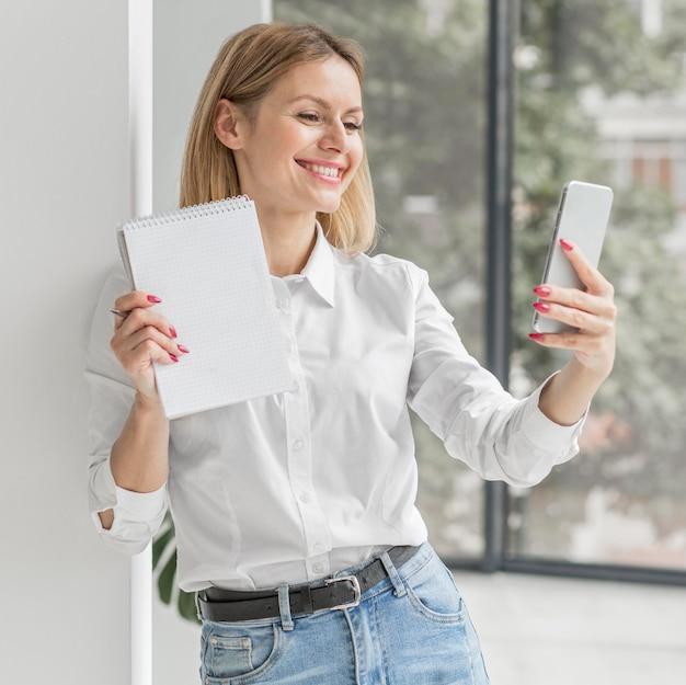 Frau, die ein selfie mit einem notizbuch nimmt