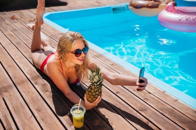 Frau, die ein selfie mit einer ananas nimmt