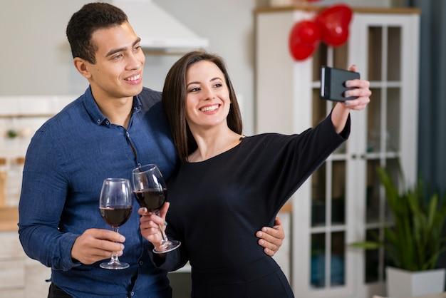 Frau, die ein selfie mit ihrem ehemann am valentinstag nimmt