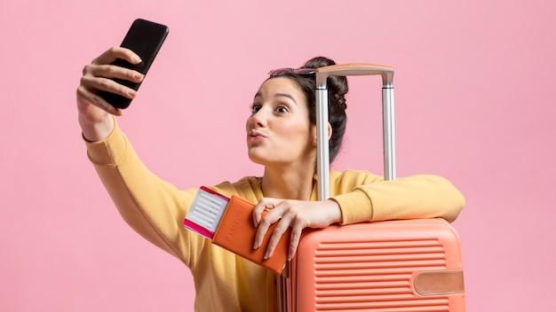 Frau, die ein selfie mit ihrem pass und gepäck nimmt