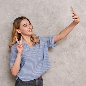 Frau, die ein selfie mit ihrem telefon nimmt