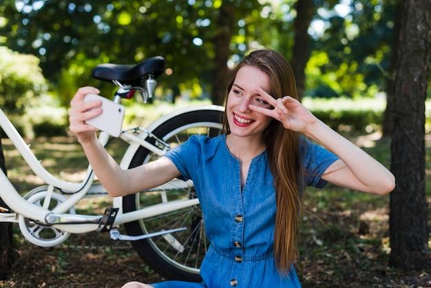 Frau, die ein selfie nahe bei ihrem fahrrad nimmt