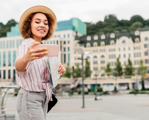 Frau, die ein selfie neben einem schönen gebäude nimmt
