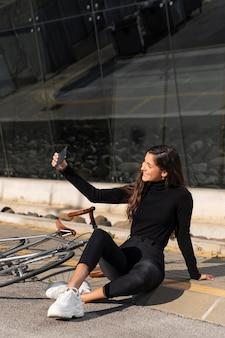 Frau, die ein selfie neben ihrem fahrrad nimmt