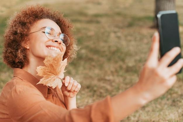 Frau, die ein selfie nimmt, während sie ein herbstblatt hält