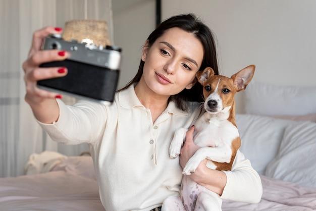 Frau, die ein selfie von ihr und ihrem hund nimmt