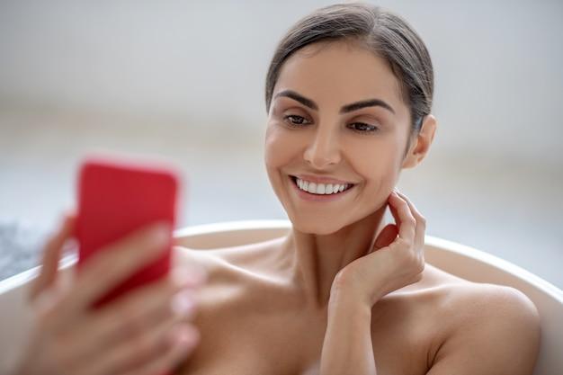 Frau, die ein smartphone beim baden verwendet