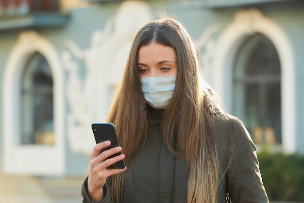 Frau, die ein smartphone benutzt, trägt eine medizinische gesichtsmaske, um die ausbreitung des coronavirus auf einer stadtstraße zu vermeiden