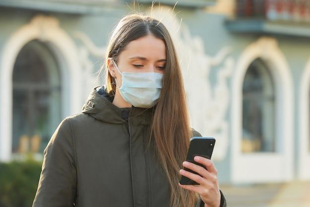 Frau, die ein smartphone benutzt, trägt eine medizinische gesichtsmaske, um die ausbreitung des coronavirus auf einer straße zu vermeiden