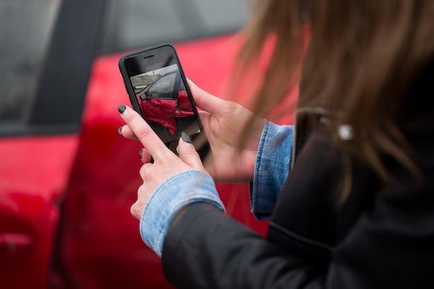 Frau, die ein smartphone benutzt, um ein foto des durch ein autounfall verursachten schadens an ihrem auto zu machen