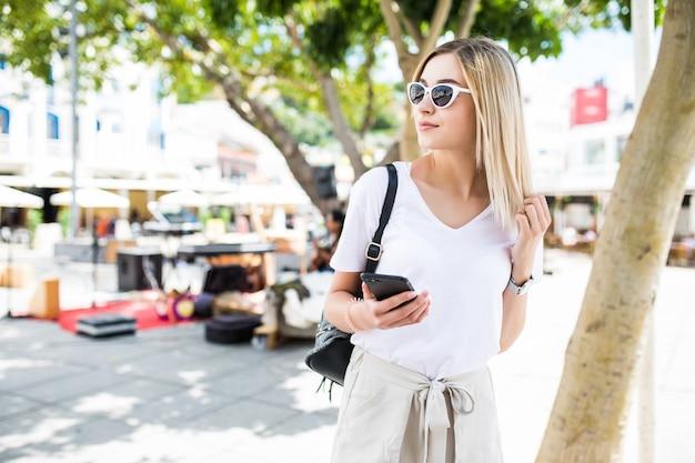 Frau, die ein smartphone in der straße an einem sonnigen sommertag geht und verwendet