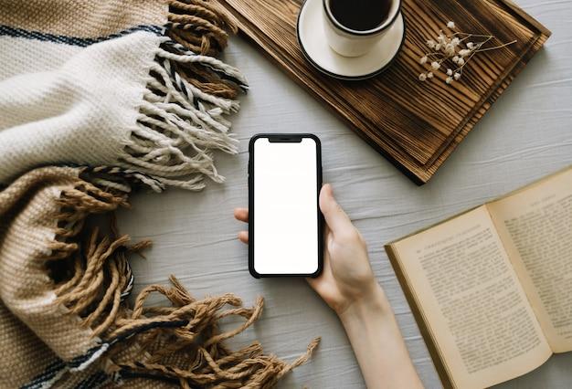 Frau, die ein smartphone mit einem weißen bildschirm verspottet, auf dem bett zu hause sitzt und kaffee trinkt.