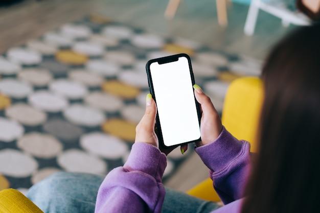 Frau, die ein smartphone mit einem weißen bildschirm verspottet, der auf dem sessel im wohnzimmer zu hause ruht.