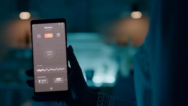 Frau, die ein smartphone mit einer intelligenten licht-app zur sprachaktivierung hält, um die lichter im haus einzuschalten. person, die zukunftstechnologie und intelligente software verwendet, die glühbirnen drahtlos einschaltet, bevor sie am laptop arbeiten