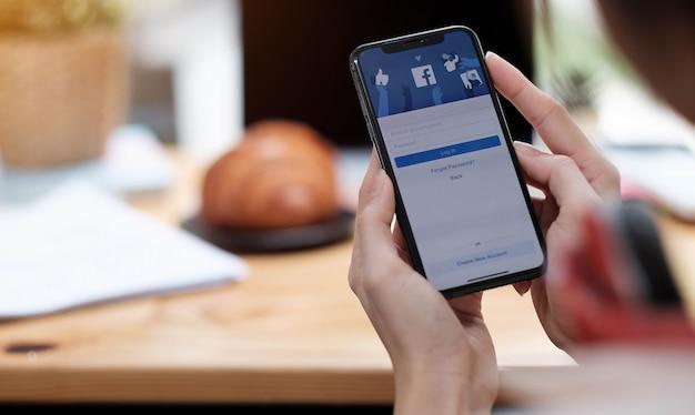 Frau, die ein smartphone mit sozialem internetdienst facebook auf dem bildschirm hält.