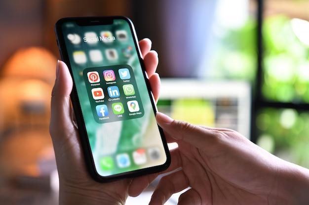 Frau, die ein smartphone mit symbolen der sozialen medien auf dem bildschirm zu hause hält
