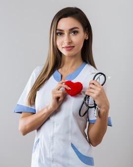 Frau, die ein stethoskop und ein plüschherz hält