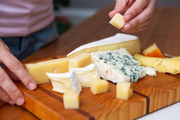 Frau, die ein stück käse vom holzbrett nimmt