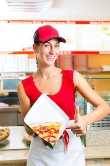 Frau, die ein stück pizza isst