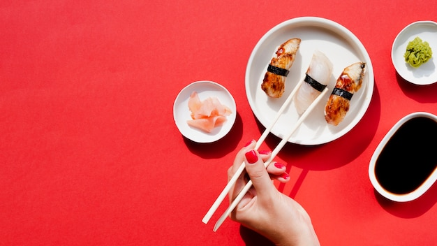 Frau, die ein stück sushi von einer weißen platte mit sushi nimmt