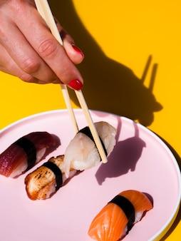 Frau, die ein sushi von einer platte mit sushi nimmt
