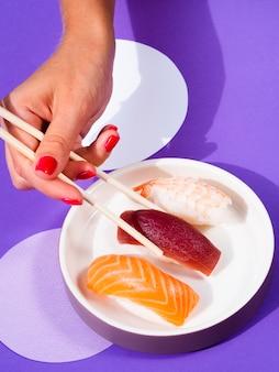 Frau, die ein thunfischsushi mit essstäbchen von der platte auswählt