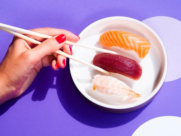 Frau, die ein thunfischsushi von einer weißen schüssel mit sushi nimmt