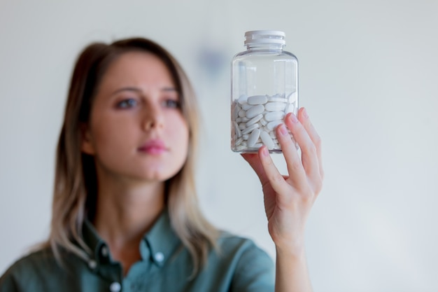 Frau, die ein transparentes glas mit weißen pillen hält.